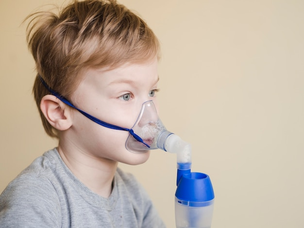 Side view boy with oxygen mask