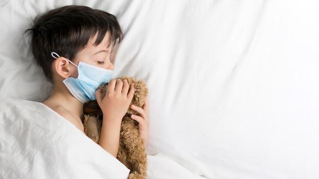 Вид сбоку мальчик с мишкой в постели
