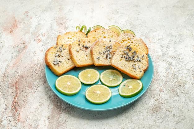 테이블에 있는 파란색 접시에 허브와 레몬을 넣은 사이드 뷰 빵과 레몬 흰 빵