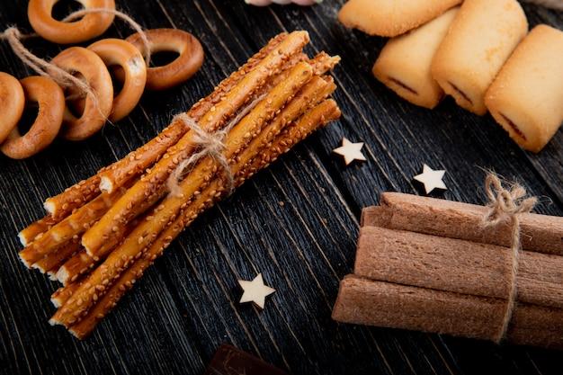 Вид сбоку хлебные палочки с печеньем сухие бублики и кукурузные палочки
