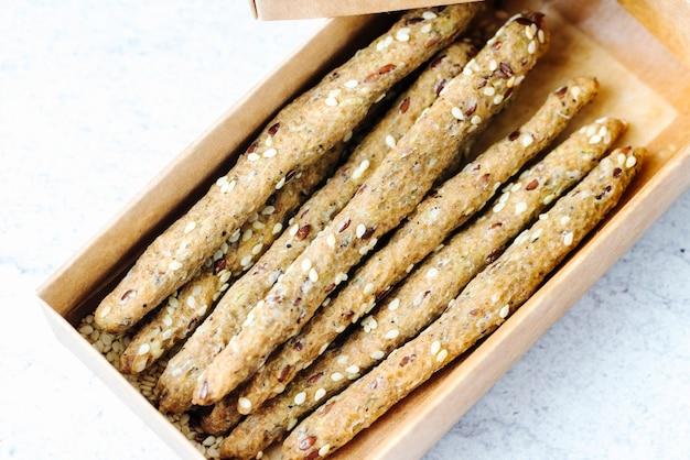 Вид сбоку хлебные палочки с кунжутом в коробке