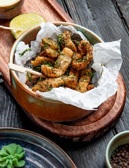 Side view of breaded chicken with herbs in a bowl with lemon and cream sauce on wood board on rustic
