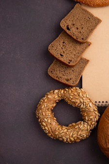 Vista laterale dei pani come fette del pane di segale e del bagel su fondo marrone rossiccio con lo spazio della copia
