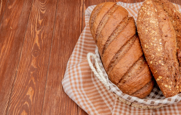 Side view of breads as black and seeded baguette in basket on plaid cloth and wooden surface with copy space