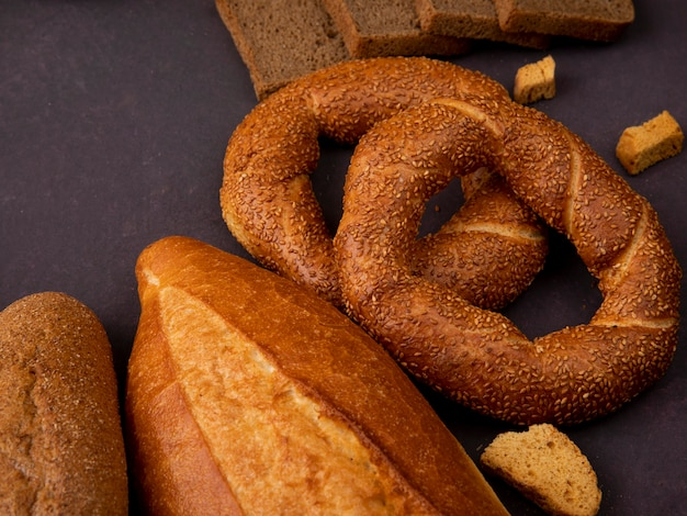 Vista laterale dei pani come bagel delle baguette del pancarrè su fondo marrone rossiccio con lo spazio della copia