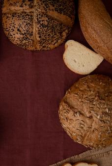 Vista laterale dei pani come fetta e bagel seminati del pane bianco della pannocchia sul fondo di borgogna con lo spazio della copia