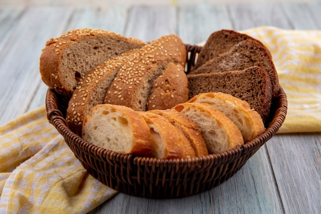 Side view of breads as sliced seeded brown cob rye and crusty ones in basket on plaid cloth on wooden background