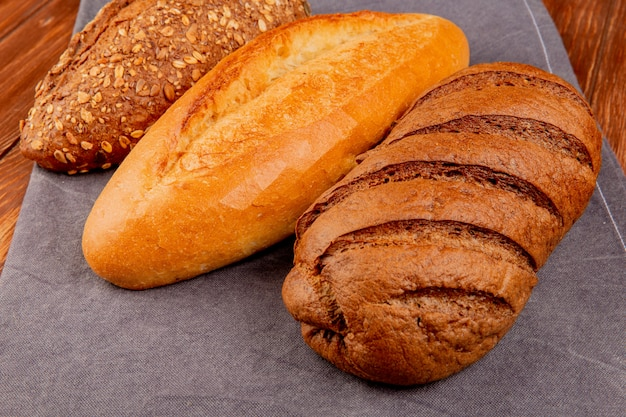 Side view of breads as vietnamese and black seeded baguette and black bread on gray cloth and wooden table