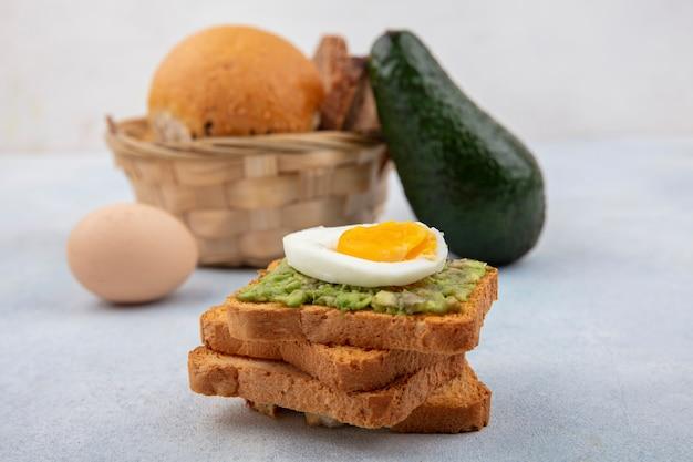 Vista laterale di pane con polpa di avocado e uovo sodo con un secchio di pane con avocado e uovo su superficie bianca