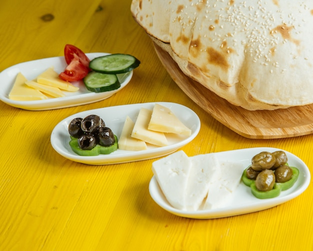 Side view of breakfast food pickled olives with cheese and fresh vegetables served with bread