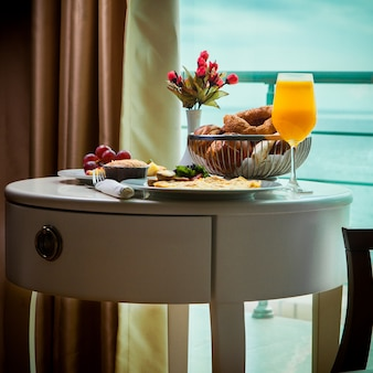 Side view breakfast omelet with mushrooms, juice, croissants in room service at hotel with amazing sea view
