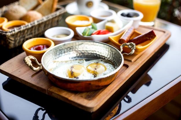 Боковой вид на завтрак, набор жареных яиц и колбас со свежими огурцами, помидорами, оливками, кетчупом, майонезом, хлебом и стаканом сока на столе