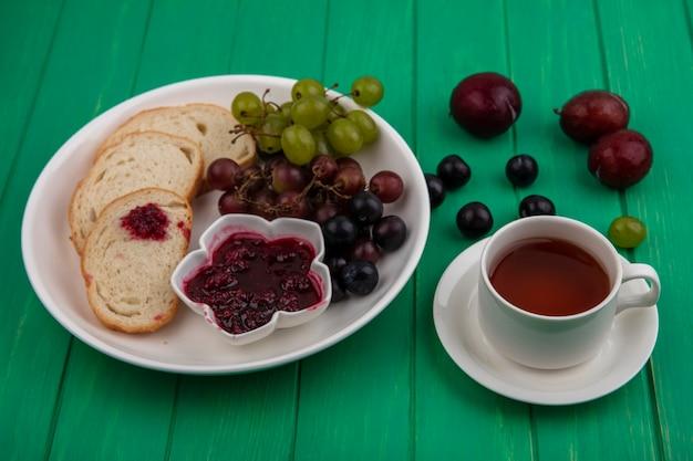 Vista laterale del set da colazione con fette di pane marmellata di lamponi e uva nel piatto e tazza di tè con pluots su sfondo verde