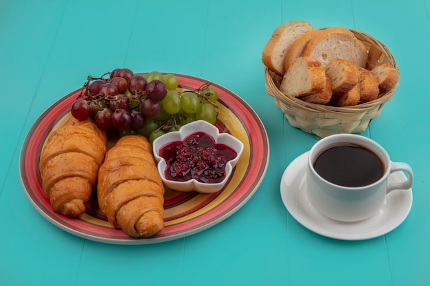 Side view of breakfast set with croissant grape raspberry jam and bread slices with cup of tea on blue background