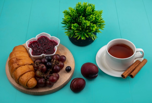 Side view of breakfast set with croissant and raspberry jam grape on cutting board and cup of tea with cinnamon and pluots plant on blue background