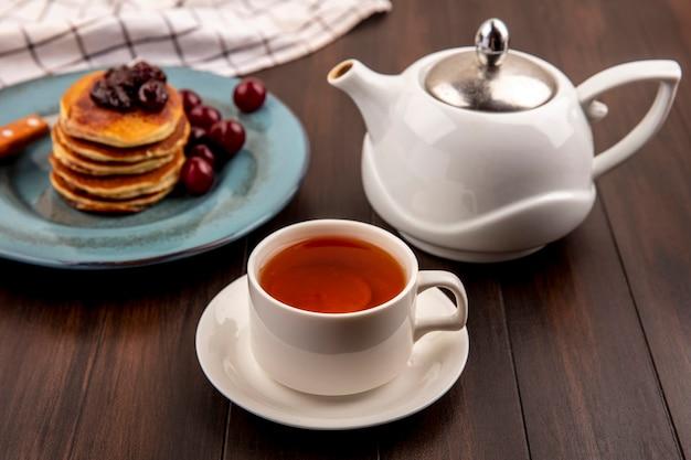 Vista laterale del set per la colazione con frittelle e ciliegie e forchetta nella piastra su plaid panno e tazza di tè con teiera su sfondo di legno