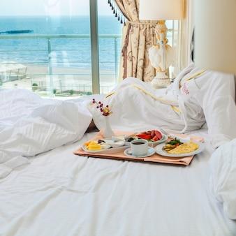 Prima colazione di vista laterale con la tazza e l'omelette di caffè in zolla su camera di albergo