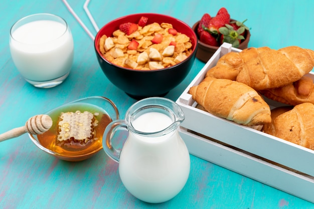Side view of breakfast with croissants, cornflakes, fruits, milk and honey on blue surface horizontal
