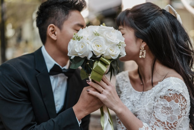 Side view of bride and groom hiding faces behind bouquet of flowers