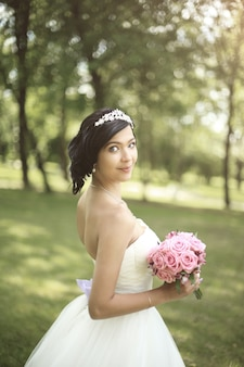 Side view. bride with bouquet standing in the park .photo with copy space