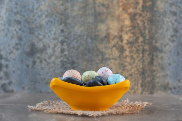 Vista laterale di caramelle di pietra multicolori luminose in una ciotola arancione.