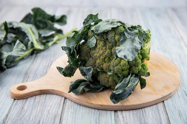 Vista laterale di broccoli e foglie di broccoli sul tagliere e su fondo in legno