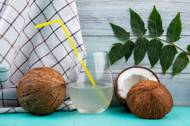 Side view of brown coconuts with a glass of water and leaf on tablecloth and grey surface