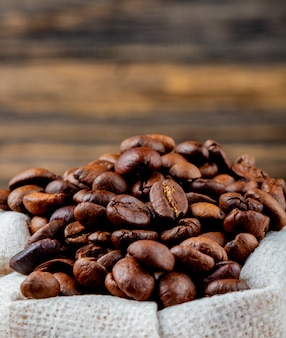 Side view of brown coffee beans in a sack on rustic table