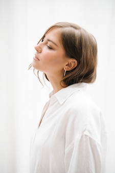 Side view of a brown hair woman in a white shirt