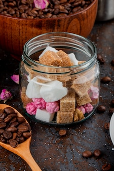 Side view of brown sugar cubes in a glass jar and coffee beans in a wooden spoon on black background