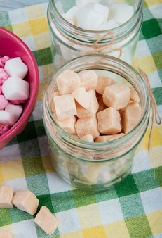 Side view of brown sugar cubes in a glass jar on plaid table napkin