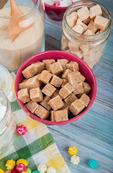 Side view of brown sugar cubes in a pink bowl and in glass jars on rustic background