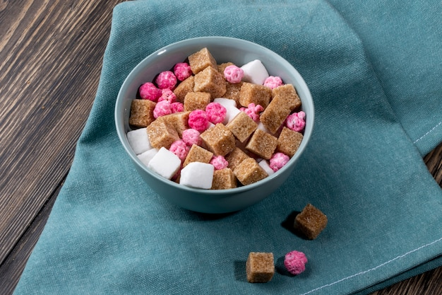 Side view of brown sugar cubes with pink candies in a bowl on blue