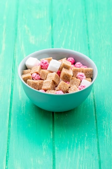 Side view of brown sugar cubes with pink candies in a bowl on green