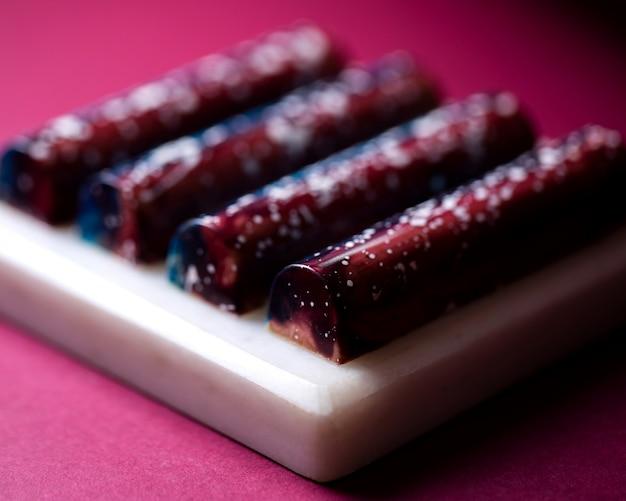 白いスタンドに茶色の白い斑点チョコレートのお菓子の側面図