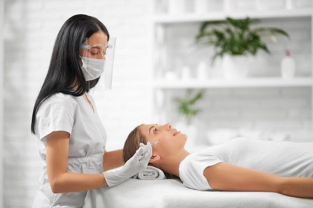 Side view of brunette beautician in protective mask doing beauty injection for improvements skin face