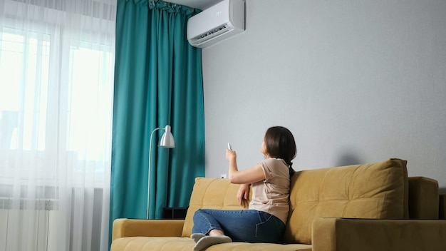 Side view of a brunette woman adjusts the air conditioner while sitting on the sofa.