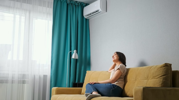 Side view of a brunette woman adjusts the air conditioner while sitting on the sofa