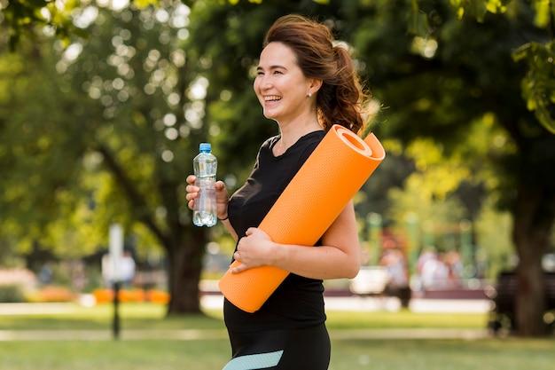 Вид сбоку брюнетка женщина, держащая коврик для йоги