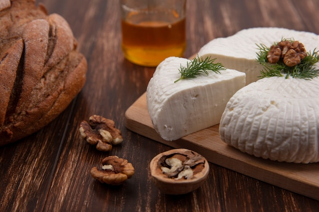 Side view bryndza cheese on a stand with walnuts and a loaf of bread on a wooden background