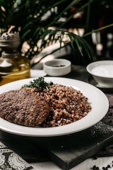 Vista laterale di grano saraceno con cotoletta di carne ed erbe sul tavolo
