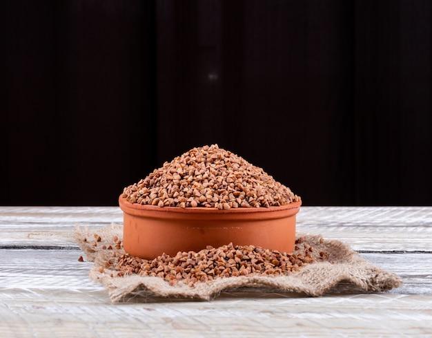 측면보기 메 밀 흰색 나무와 검은 배경에 아래 메 밀 자루 헝겊에 그릇에. 텍스트 가로 공간