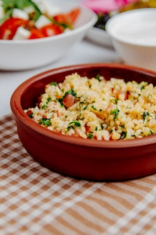 Side view of bulgur with tomatoes in a wooden bowl