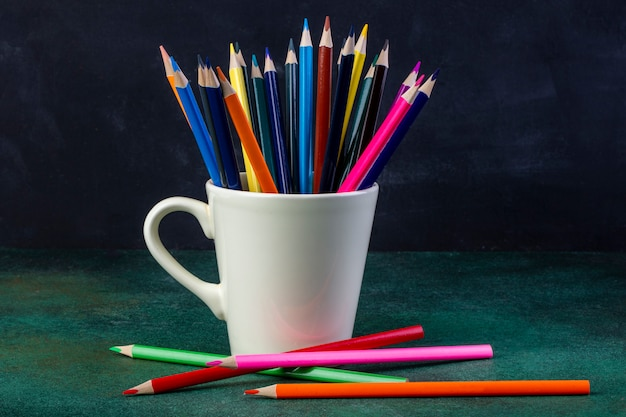 Side view of a bunch of colored pencils in a white cup on dark
