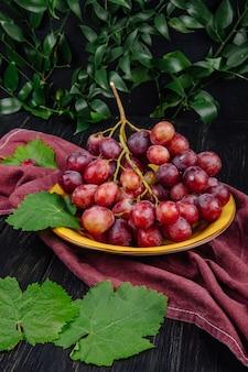 Vista laterale di un grappolo di uva dolce fresca in un piatto e foglie di vite verde sul tavolo di legno