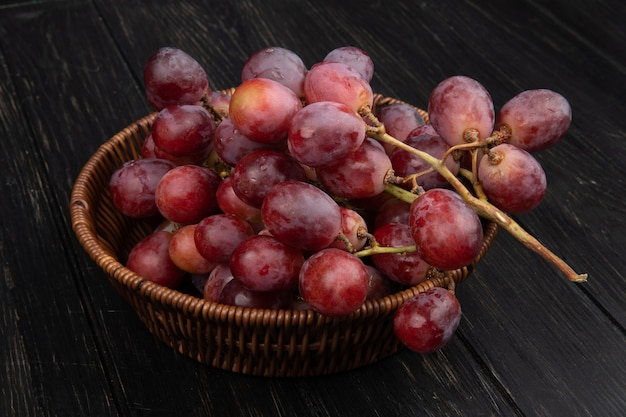 Vista laterale di un grappolo di uva dolce fresca in un cesto di vimini sul tavolo di legno scuro