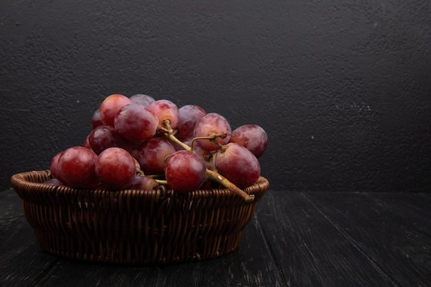 Side view of a bunch of fresh sweet grapes in a wicker basket on dark wooden table