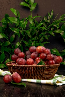 Vista laterale di un mazzo di uva dolce fresca in un canestro di vimini sulla tavola delle foglie verdi