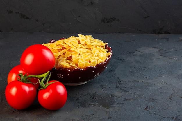 Вид сбоку гроздь томатов с тарелкой макаронных бантиков