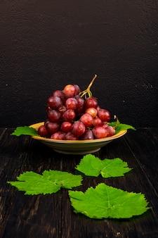 Vista laterale di un grappolo di uva dolce in un piatto e foglie di vite verde sul tavolo rustico
